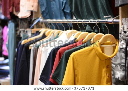Clothes on clothes rail in clothing store - stock photo