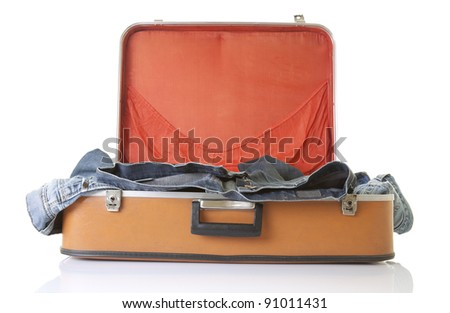 Clothes on old fashioned suitcase - stock photo