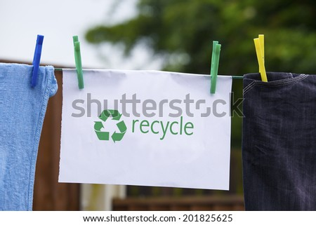 Clothes pegged on a washing line with recycle sign. - stock photo