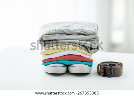clothes, personal staff and objects concept - close up of folded shirts, pants, belt and shoes on table at home - stock photo