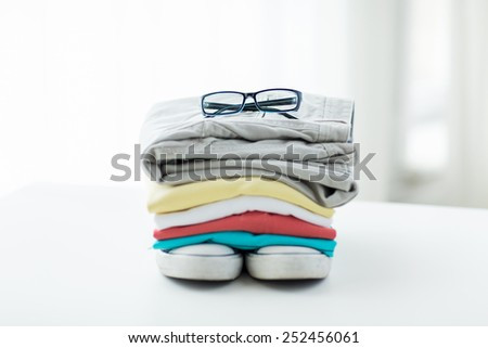 clothes, personal staff and objects concept - close up of folded shirts, pants, glasses and shoes on table at home - stock photo