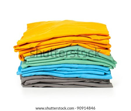 clothes pile. Bright folded clothes on white background. - stock photo