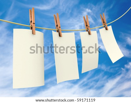 Clothes pin holding white sheets of paper outdoors - stock photo