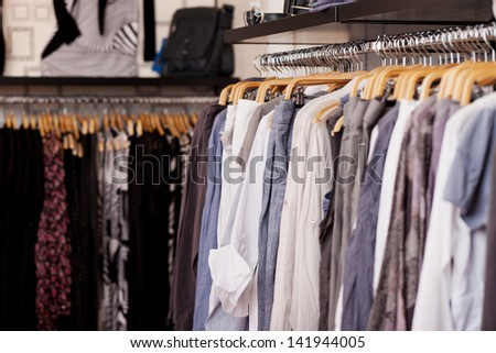 Clothes rack full of clothes in clothing store - stock photo