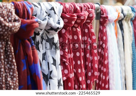 clothes rack with a selection of scarves or scarfs - stock photo
