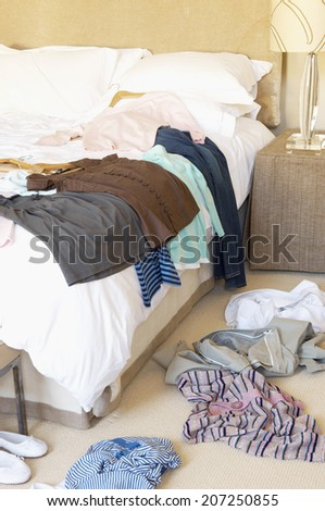 Clothes scattered on the floor and bed in the hotel room - stock photo