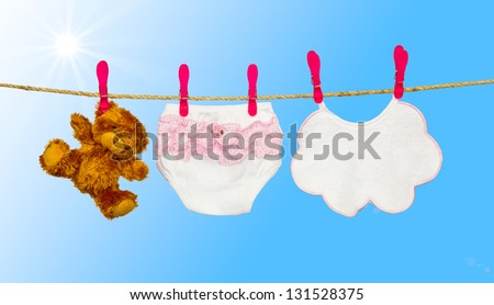 clothesline with baby clothes and teddy bear