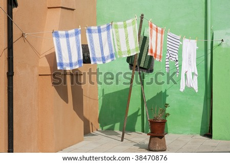 Clothesline with laundry in front of colorful walls.