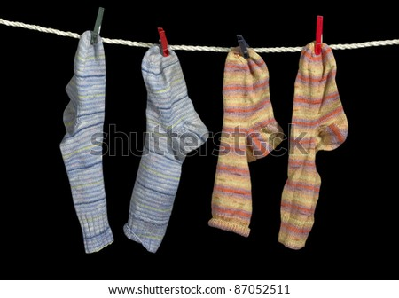 clothesline with some multicolored sox fixed with clothes pins in black back