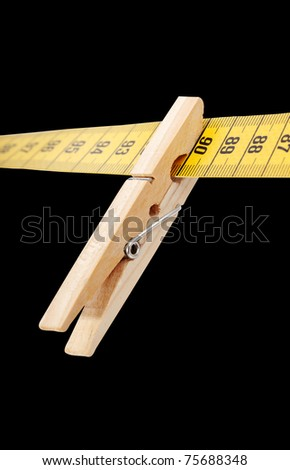 Clothespin and measuring tape isolated on a black  surface. - stock photo