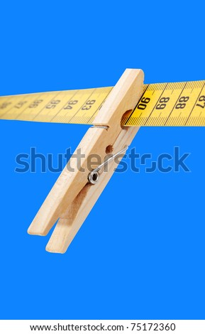 Clothespin and measuring tape isolated on a blue surface. - stock photo