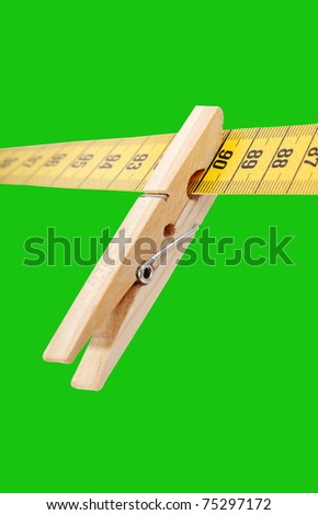Clothespin and measuring tape isolated on a green surface. - stock photo