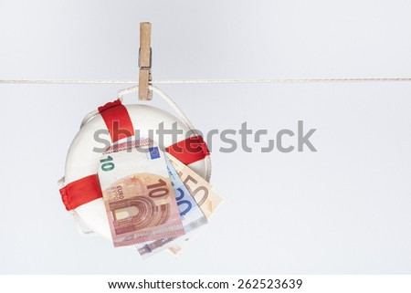 clothespin fixing a safety buoy with euro banknotes on a clothes line. financial concept for currency risk or protection  - stock photo