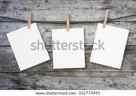 clothespin hanging with blank paper on wooden background - stock photo