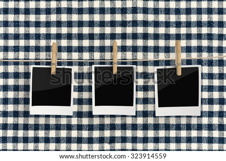 clothespin hanging with blank photo paper on tartan background - stock photo