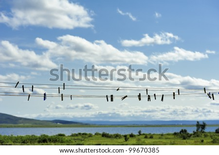 clothespins hanging on empty rope outdoor - stock photo