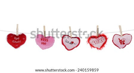 Clothespins holding five red. white and pink mini-heart pillows on a clothesline.  On a white background. - stock photo
