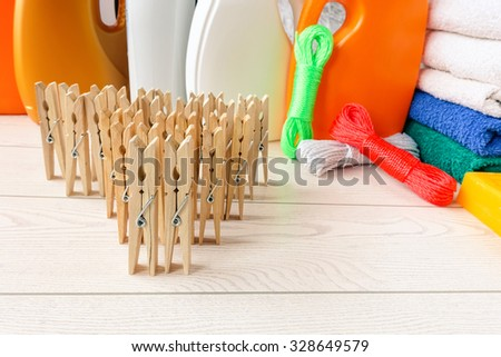 Clothespins string and detergent bottle composition - Mix of colored articles for laundry housework - Wood clothes pegs and washing products - Teamwork metaphoric concept focus on top of first clips - stock photo