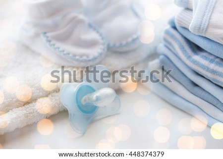 clothing, babyhood, motherhood and object concept - close up of baby soother, bootees and pile of clothes for newborn boy with holidays lights - stock photo
