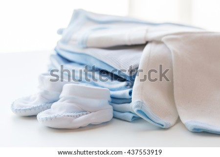 clothing, babyhood, motherhood and object concept - close up of white baby cardigan with bootees and pile of clothes for newborn boy - stock photo