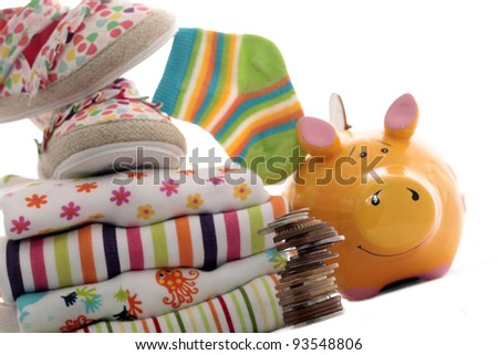 Clothing for babies and piggy bank - stock photo