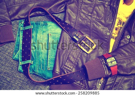 Clothing items and accessories: blue jeans with a leather belt, leather jacket, T-shirt, watches - stock photo