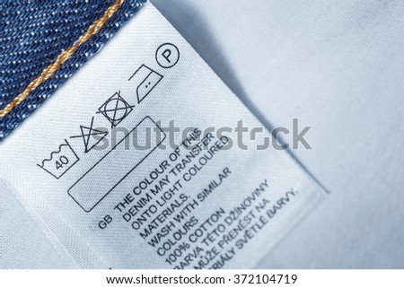 Clothing label with laundry care instruction, close up - stock photo