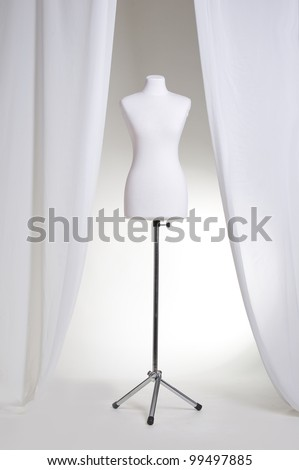 Clothing mannequin white on a light background near the curtains - stock photo