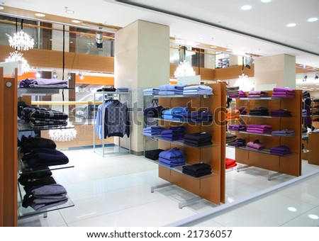 Clothing on shelfs in store - stock photo