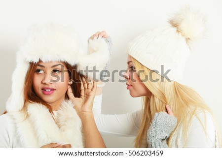 Clothing people fashion concept. Two ladies with winter outfit. Blonde woman together with mulatto girl, wearing white warm clothes.
