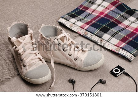 Clothing set. Womens sneakers and plaid shirt with lace insertion and black music player with headphones. Trendy lace insertion.