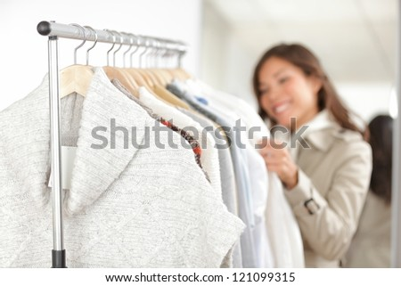 Clothing. Woman shopping clothes in store looking at clothing rack. Focus on winter sweater in foreground.