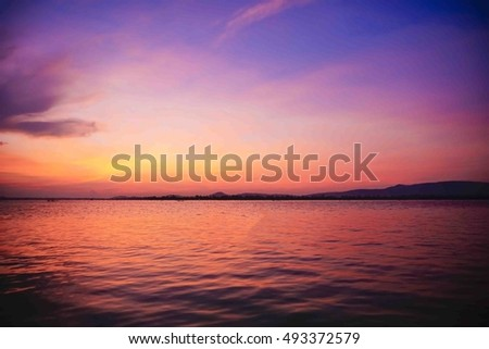 cloud and sky over lake before sunrise and water reflection at southern Thailand,select focus at stone on foreground,ideal use for background,dark edges image.