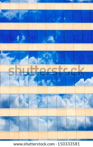 Cloud and sky reflection in the windows of modern office - stock photo