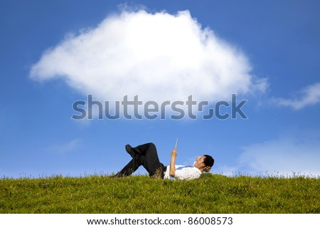 cloud background and happy businessman working with tablet pc on the green grass - stock photo