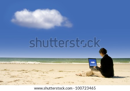 Cloud Computing: businesswoman with business suit working at the beach - stock photo