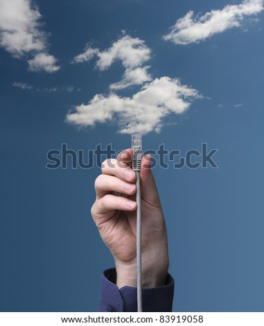 Cloud computing concept. Hand with ethernet cable connecting into cloud. - stock photo