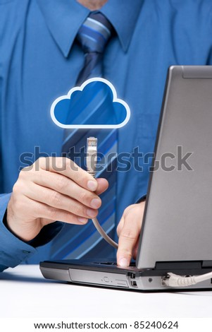Cloud computing concept. Man send data from laptop to cloud represented by icon via ethernet cable. Selective focused on cable. - stock photo