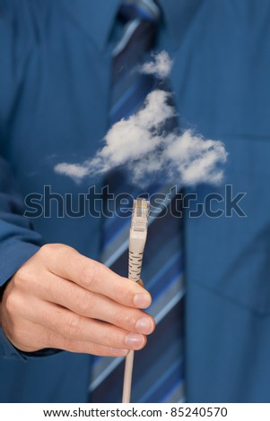 Cloud computing concept. Mans hand with ethernet cable connecting into cloud. Selective focused on cable. - stock photo