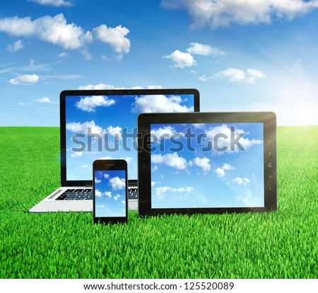 Cloud computing concept on different electronic devices. Tablet computer, laptop and smartphone in the middle of the field with sky image on screen. - stock photo