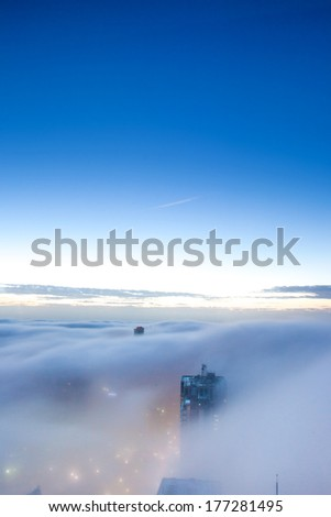 Cloud covered the high-rise buildings in Sydney Australia during early morning - stock photo