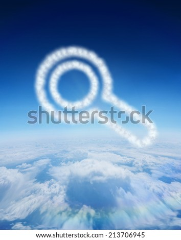 Cloud in shape of magnifying glass against blue sky over clouds at high altitude