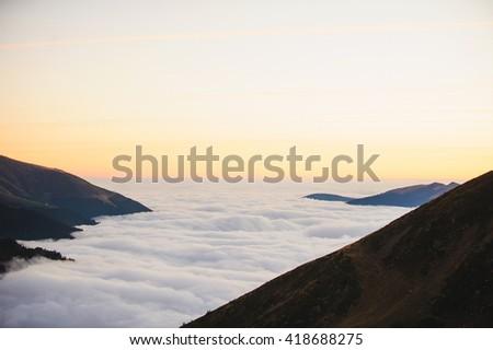cloud ocean between mountains - stock photo