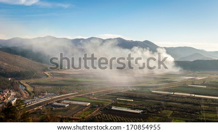Cloud of smoke over the valley - stock photo