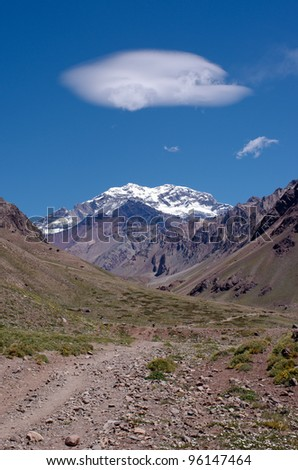 Cloud over the Aconcagua pick on the path to Plaza de Mulas base camp. Aconcagua Provincial Park, Mendoza, Argentina, South America. - stock photo