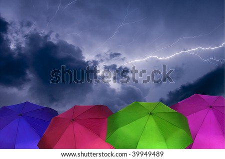 Cloud to Cloud Lightning Strike During a Thunder Storm With colorful Umbrellas in the Foreground - stock photo