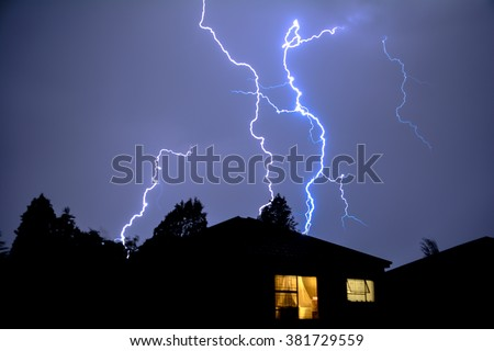 Cloud to Ground Electric Lightning behind house roof tops - stock photo