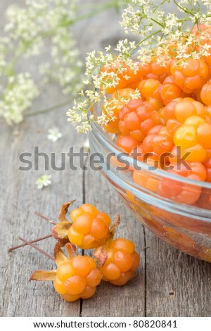 Cloudberry on wooden background with flowers - stock photo