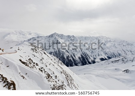 Clouded snowy winter landscape in the alps - stock photo
