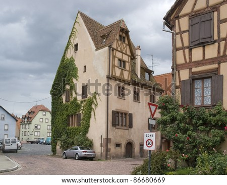 clouded street scenery with overgrown timbered houses in Selestat - stock photo